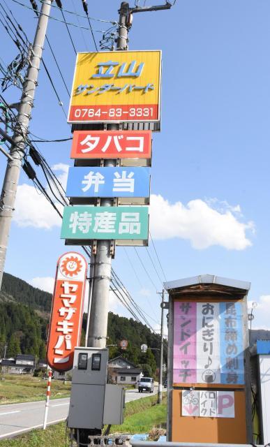 道沿いに、カラフルな看板が立つ=2018年4月12日、富山県立山町