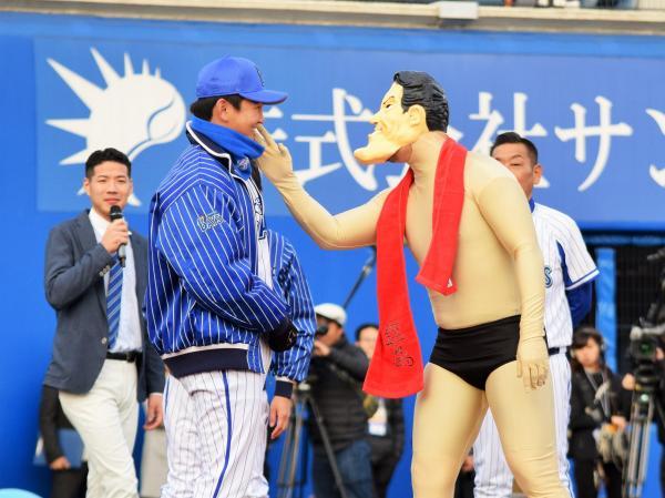 あのレスラーが? いや違って、かぶり物をつけたプロ野球・DeNAの後藤武敏選手(右)が山崎康晃選手にカツ
