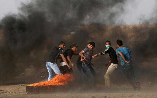 2018年5月25日、パレスチナ自治区ガザ地区とイスラエルの境界付近で、タイヤを燃やして抗議デモをするパレスチナ人=ロイター