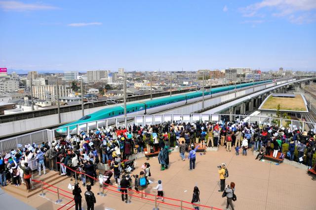北海道新幹線の開業日、屋上から列車に手を振る人たち=鉄道博物館