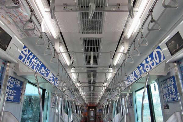 一見すると何も書かれていないように見える電車の中吊り広告。よく見ると、透明紙の上に立体的な水滴のようなものが付いています