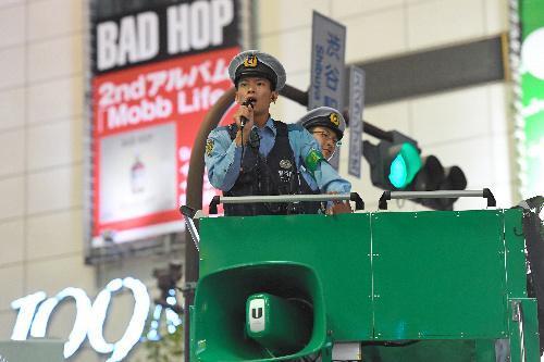 W杯出場を決めて渋谷駅前で喜ぶ人々に向け、車上から注意を呼びかけるDJポリス=2017年8月、東京・渋谷、北村玲奈撮影