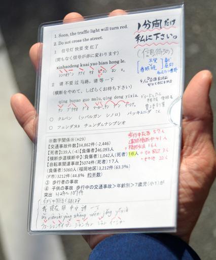 横断歩道を渡る時の注意などが4カ国語で書かれたメモ=2018年4月、北九州市