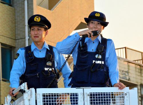 マイクを持ち観覧客に注意を促す警察官=2015年8月、富山市安野屋町2丁目