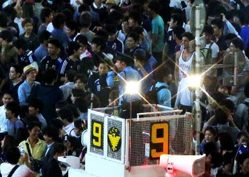 渋谷駅前の交差点で、サポーターに拡声機で呼びかける警察官=2013年6月、東京都渋谷区