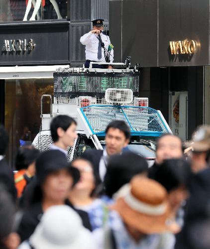 リオ五輪・パラ合同パレードを待つ人たちに呼びかける警察官=2016年10月、東京・銀座、西畑志朗撮影