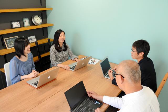 「西中藩」のコワーキングオフィスで星野翠さん(左から2人目)と話す中野智哉社長(同3人目)。「これどうしたらいいでしょう」と星野さんが気軽に相談していた=大阪市淀川区