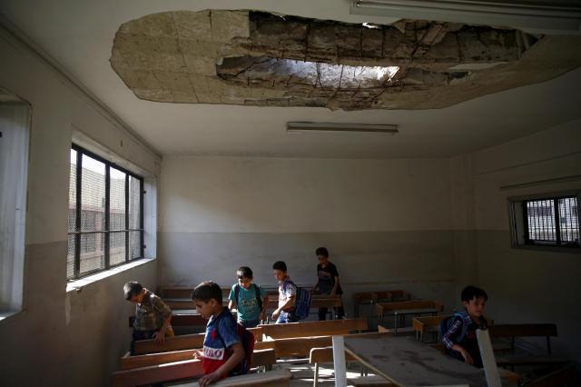 シリア・東グータ地区で、内戦の影響で天井が壊された教室に入る子どもたち=2017年9月、ロイター