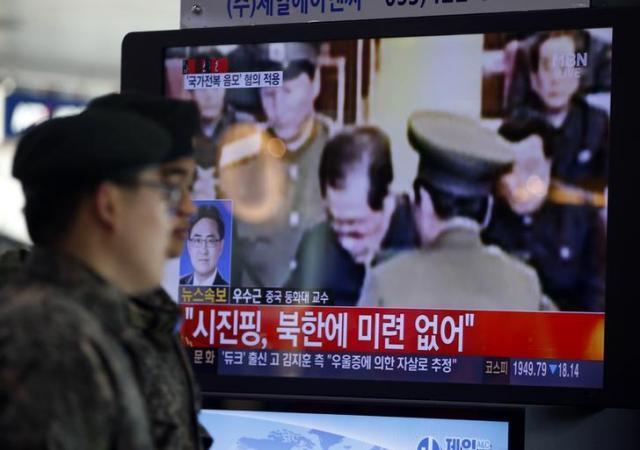 張成沢氏の処刑を伝えるニュースを映すテレビの前を通り過ぎる韓国の兵士=2013年12月、ロイター
