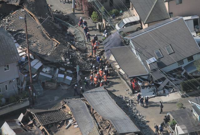 熊本地震で倒壊した家屋の近くで活動する消防隊員ら=2016年4月15日、熊本県益城町