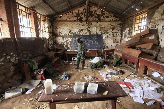 コンゴ民主共和国の町で、放棄された学校の教室を歩く反政府軍の兵士=2012年7月、ロイター