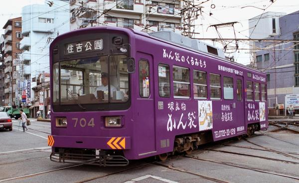 地元企業の広告を車体全面につけて走る阪堺電車 =1999年、大阪市阿倍野区