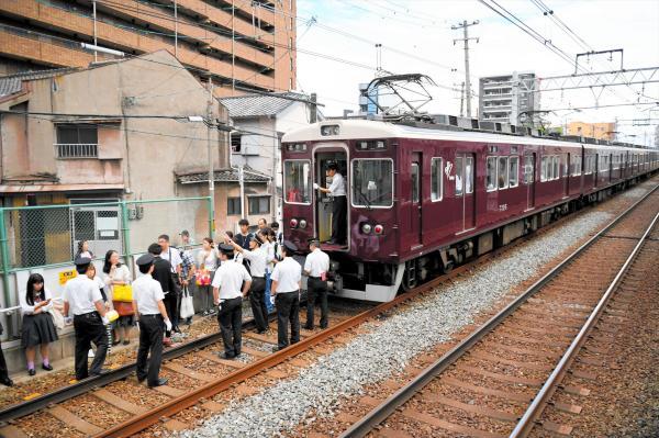 阪急千里線の線路上で停車した列車から下車する乗客ら=2018年6月18日、大阪市北区、小林一茂撮影