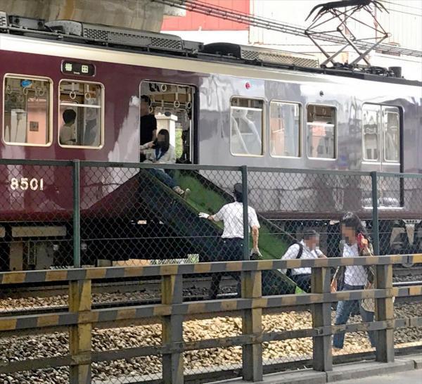 地震が発生し、阪急電鉄神戸線の駅と駅の間で緊急停止した車両から座席シートを滑って降りる乗客=2018年6月18日、阪急電鉄提供(乗客の顔にモザイクをかけています)