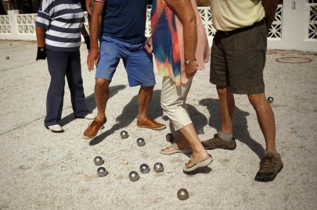 スペインのベナルマデナでペタングをする人々=ロイター