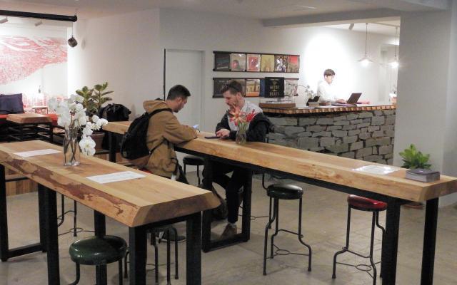 一枚板のテーブルが並ぶロビー。奥は青石で作ったフロント=東京都渋谷区