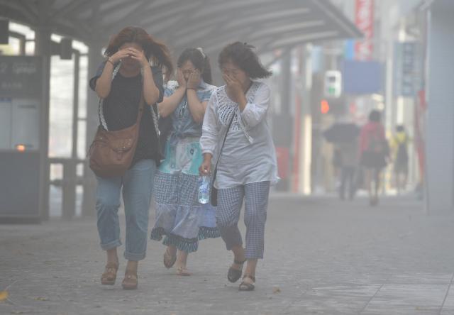降り積もった火山灰が風で吹き上げられ、市街地は白く煙っていた=2013年8月19日、鹿児島市