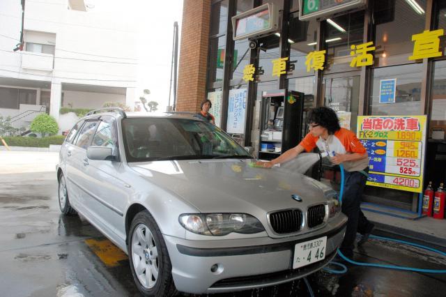 車についた灰を洗い流すガソリンスタンド店員=2009年4月10日、鹿児島市東郡元町