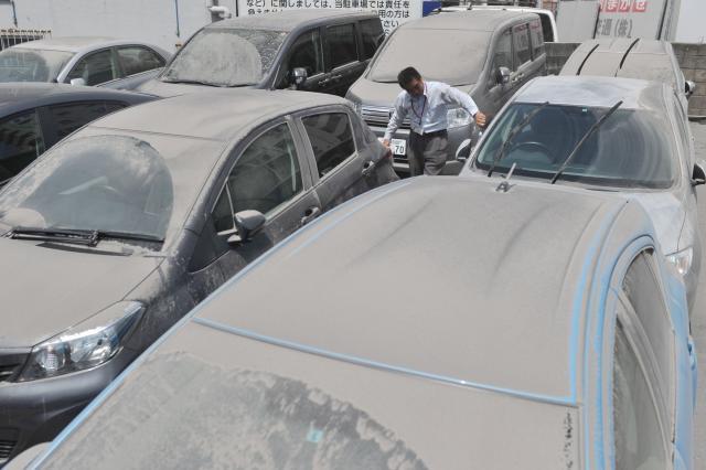 火山灰に覆われたレンタカー店の車=2013年8月19日