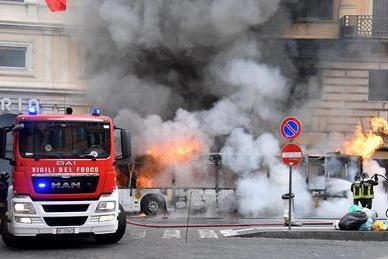 炎を上げて燃える路線バスを消化する消防隊