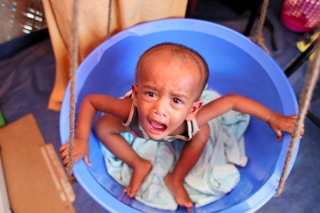 バケツに入って、体重を量られるイスラム教徒ロヒンギャの子ども。難民キャンプでは栄養失調の子どもが多いという=2017年11月、バングラデシュ・コックスバザール