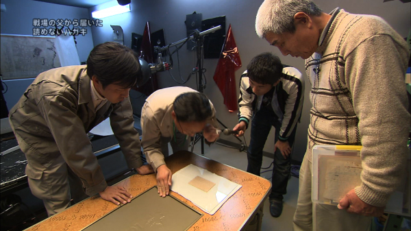 番組の中で、はがきに書かれた文字を見る馬場基さん(左)ら=朝日放送テレビ提供