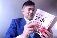 40万部の大ヒットとなった自分の本を複雑な表情で読む田村耕太郎さん