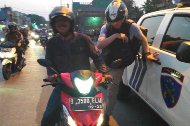 ジャカルタにて、バイクタクシーを降りる野上記者