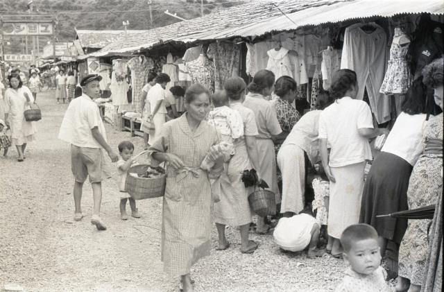 1955年6月25日に奄美大島が日本に復帰して2年目。復帰の日をちょうど半年後に控えた名瀬の商店街は、多くの買い物客でにぎわっていた