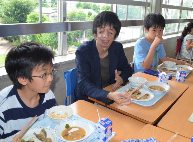 子どもたちと給食を食べる石田さん(中央)