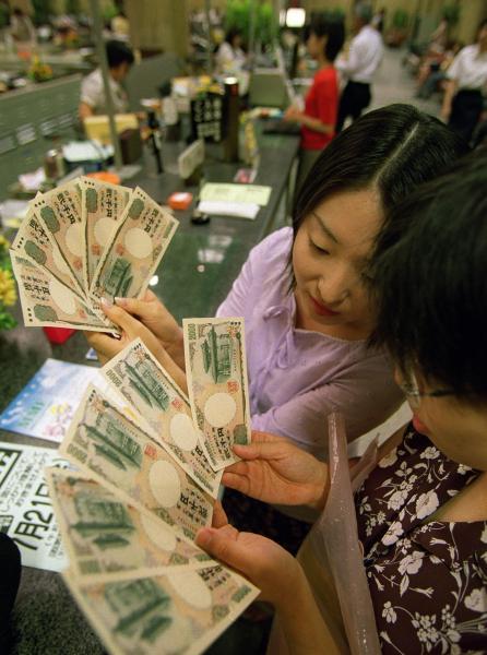 1万円を2千円札5枚に交換して新札の感触を確かめ合い、「ちょっと使うのはもったいないわね」と話す女性たち=2000年7月19日