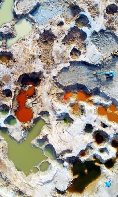 産業廃棄物の投棄痕がむき出しになっている処分地。産廃の影響で穴にたまる地下水や雨水が様々な色に染まっていた=2018年1月10日、香川県・豊島、池田良撮影