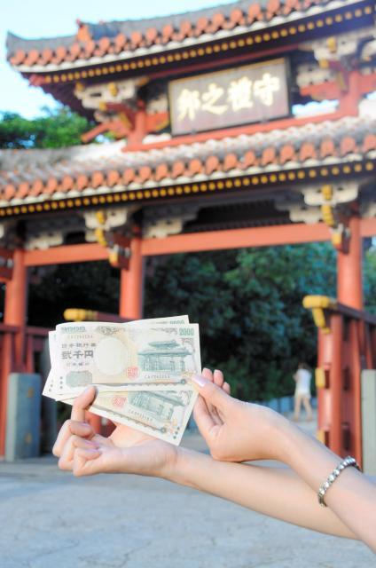 2千円札と守礼門=那覇市