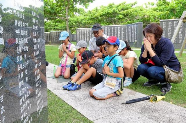 親族の名前が刻まれた平和の礎の前で、手を合わせる夫婦と子どもたち=2018年6月23日午前、沖縄県糸満市の平和祈念公園