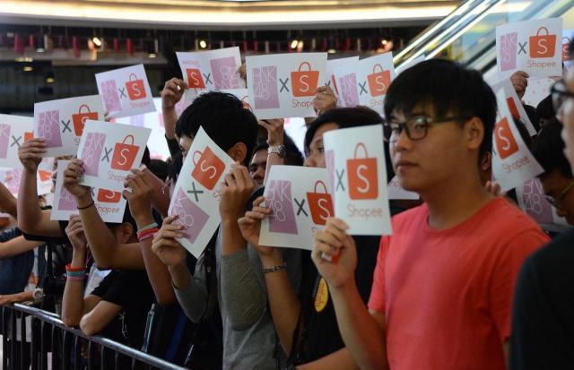 BNK48と書かれた紙を掲げる人たち。イベントのために10時間待った人もいたという=2018年6月、バンコク