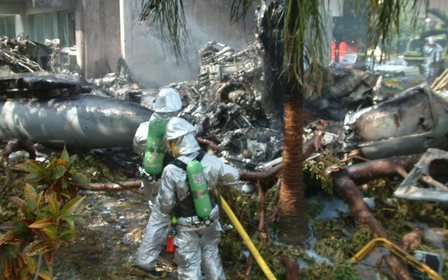 米軍ヘリの墜落現場。機体は炎上し、原形をとどめていない。後ろはヘリがぶつかった沖縄国際大学1号館=2004年8月13日、沖縄県宜野湾市
