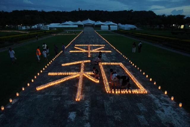 慰霊の日の前夜、ろうそくの火で「平和」の字がともされた=2018年6月22日午後7時43分、沖縄県糸満市の平和祈念公園