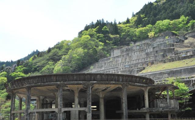 円形の建物。奥の山の斜面には、ひな壇状にコンクリートの基礎部が残っている