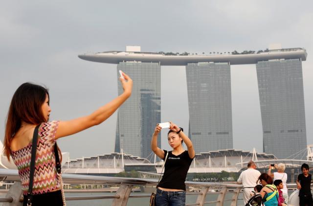 シンガポールの観光名所になっているリゾートタワー「マリーナ・ベイ・サンズ」を背景に記念撮影する女性ら=ロイター