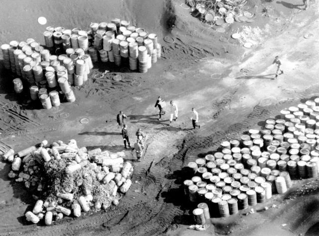 豊島に不法投棄されたドラム缶などを調べる兵庫県警の捜査員=香川県土庄町、1990年11月、朝日新聞社ヘリから