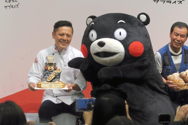 世界大会で優勝した台湾のパン職人陳耀訓さん(左)とふれあうくまモン、陳さんの回答は「熊本熊」だった=2018年6月19日、熊本市中央区のくまモンスクエア