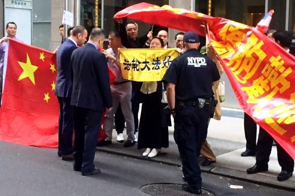 ニューヨークで「法輪功」のメンバーらが持っている黄色の横断幕を覆い隠そうとする中国共産党支持派=2015年9月26日、峯村健司撮影
