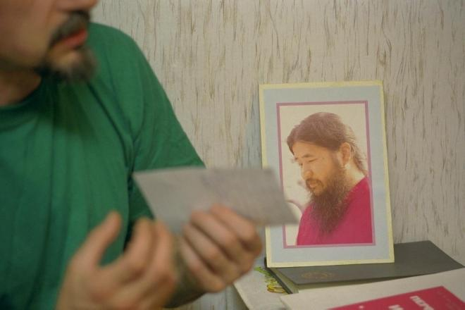 1995年5月、モスクワ市内で朝日新聞の取材に答えるロシアのオウム真理教信徒。ロシア政府による活動停止命令のあとも、麻原代表の肖像を自宅に飾っていた