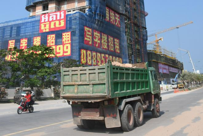 中国資本が建設中の高層ビルの前を走行する工事車両=2018年2月9日、益満雄一郎撮影