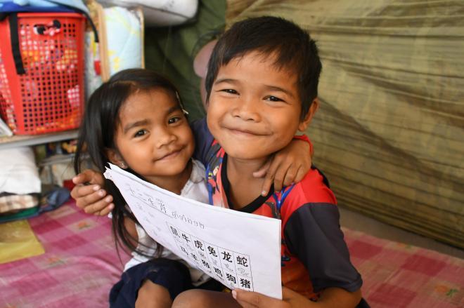 中国語を勉強するジョム・ジャンリー君(右)と、仲良しの妹のジョム・スレイイーちゃん。年齢は4歳離れているが、誕生日は同じ=2018年2月10日、益満雄一郎撮影