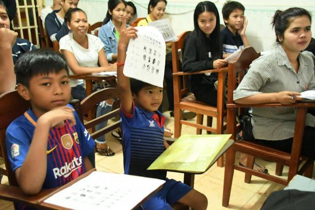 中国語の授業中、問題用紙を持ち上げて先生に見せるジャンリー君=2018年2月8日、益満雄一郎撮影