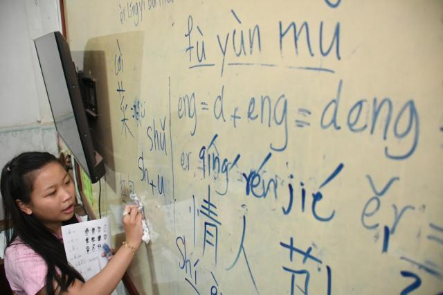 中国語を教える高校生のオン・スィディエンさん。自身ももともとこの学校の生徒=2018年2月8日、益満雄一郎撮影