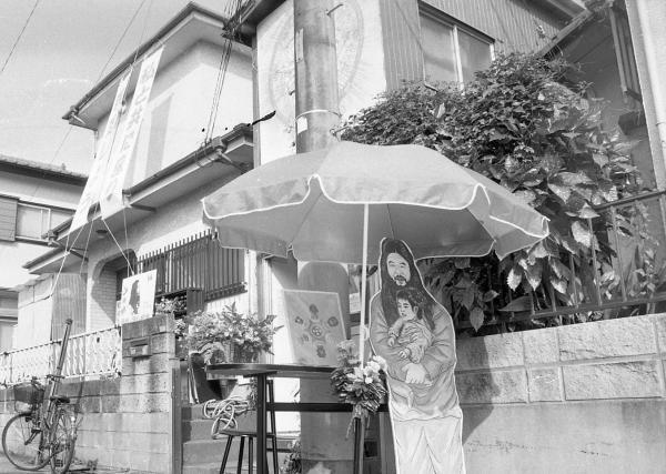 支部手前の道路に置かれた、教団代表だった松本死刑囚をかたどったボード=1995年8月