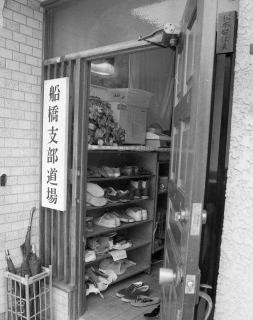 オウム真理教船橋支部の玄関には信徒たちの靴が並び、右上に「松本智津夫」の表札がかかっていた。かつて松本死刑囚の一家が住んだ=1995年8月、千葉県船橋市