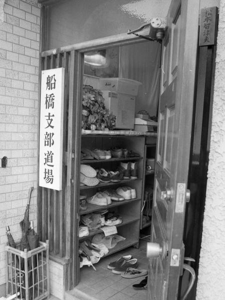支部の玄関には信徒たちの靴が並び、右上に「松本智津夫」の表札がかかっていた。かつて松本死刑囚の一家が住んだ=1995年8月